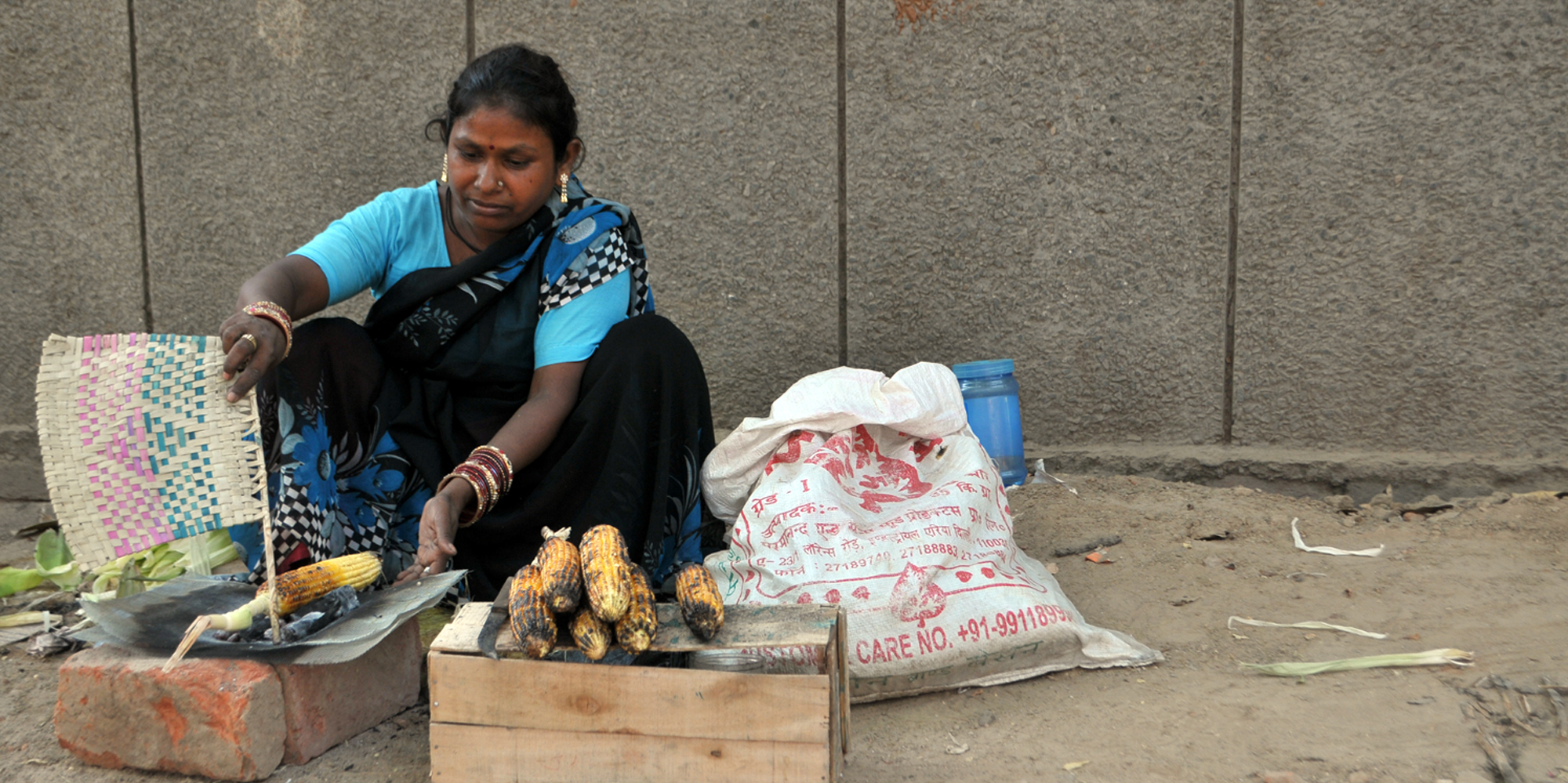 <strong>Corn Seller A woman prepares corn to sell near Connaught Place, Delhi</strong> -
